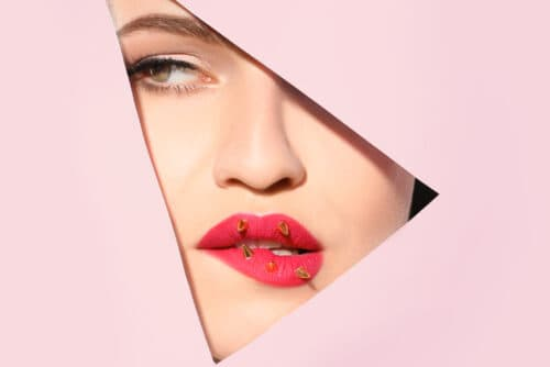 View of beautiful young woman with creative lips makeup through cutout in color paper